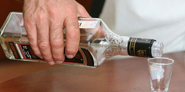 Наполнение рюмки из бутылки алкоголем