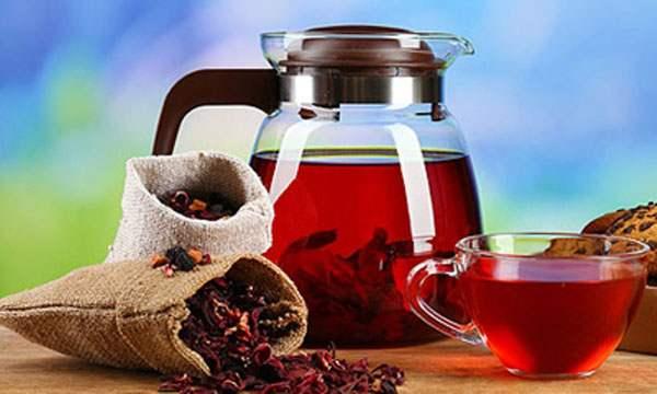 Заваренный чай каркаде рядом с сухими лепестками
